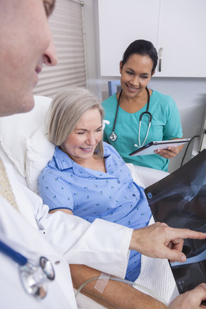 A happy senior female woman elderly patient in bed looking at X-ray of a hip replacement with male doctor and Hispanic nurse Banco de Imagens