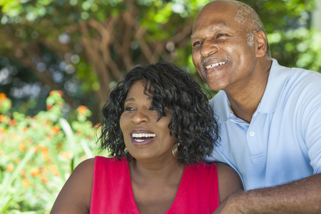 A happy senior African American man and woman couple in their sixties outside together smiling. photo