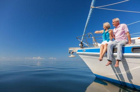 A happy senior couple sitting on the side of a sail boat on a calm blue sea