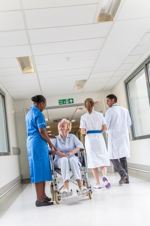 Senior female woman patient in wheelchair sitting in hospital corridor with African American female nurse Banco de Imagens