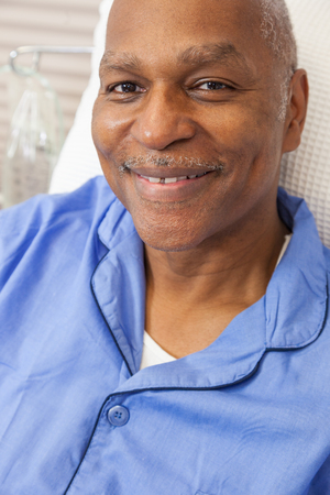 Happy senior African American man male patient recovering in hospital bed with wearing blue pajamas Banco de Imagens
