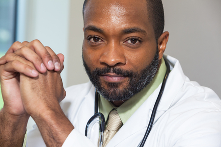 An African American doctor in a white lab coat with a stethoscope Banco de Imagens