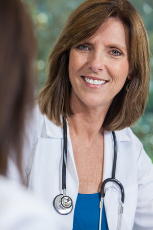 A happy smiling middle aged female doctor with a stethoscope sitting at a meeting with colleague in a hospital office