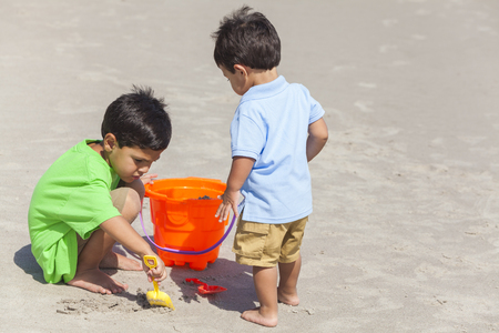 Two happy young hispanic boys brothers playing together on a sunny tropical beach with buckets and spades making sandcastles