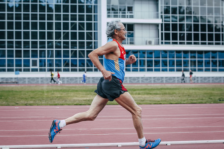 65 years old: Chelyabinsk, Russia - August 28, 2015:  old male athlete running during championship of Russia on track and field athletics among the elderly, Chelyabinsk, Russia - August 28, 2015