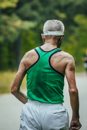 jogging track: old man runs back in sweat