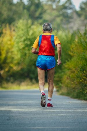 jogging track: old male athlete running alone on the road in the Park Stock Photo