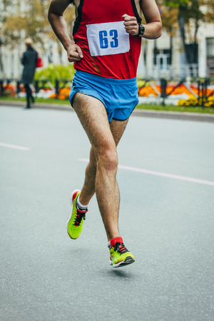 without legs: male athlete running on a city street during the marathon Stock Photo