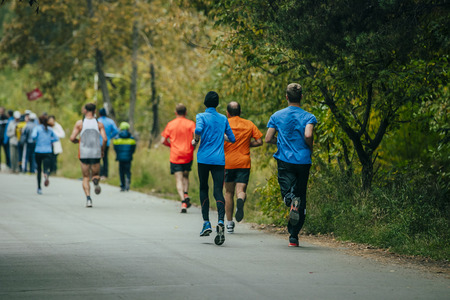 jogging track: male athletes running in the autumn Park