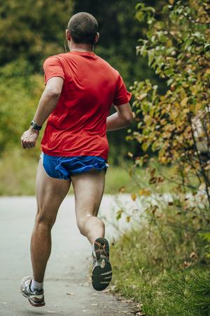 uomo rosso: atleta di sesso maschile in una camicia rossa che attraversa il parco Archivio Fotografico