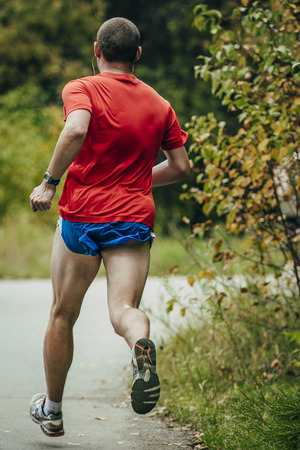 man rear view: male athlete in a red shirt running through the Park Stock Photo