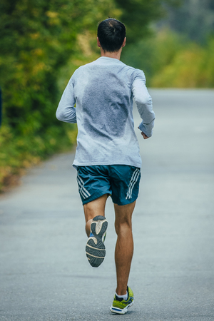 man rear view: athlete runs through the Park, an asphalt road, in a sweat shirt