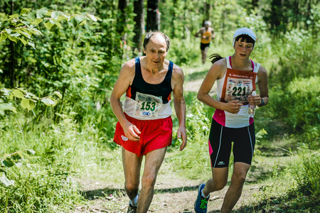 hyperhidrosis: Miass, Russia - June 28, 2015: old man and the girl run during marathon Running clean water-2015, Miass, Russia - June 28, 2015 Editorial
