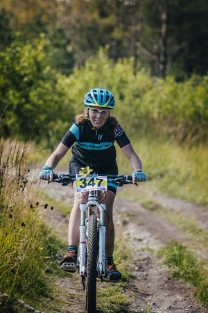 mountain bicycling: V.Ufaley, Russia - August 09, 2015: girl racer on bike rides on the trail during race Big stone, V.Ufaley, Russia - August 09, 2015