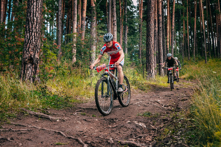 Miass, Russia - July 19, 2015: three bikers in the mountains by downhill during race