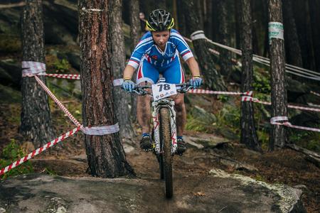 mountainbike: Sludorudnik, Russia - August 06, 2015:  girl mountainbike down the stones during Spartakiada among boys and girls in Cycling-mountain bike, Sludorudnik, Russia - August 06, 2015