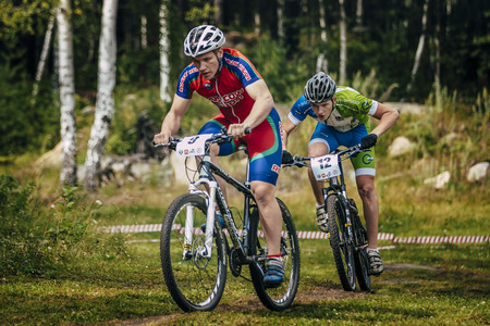 Sludorudnik, Russia - August 06, 2015:  two cyclists compete during Spartakiada among boys and girls in Cycling-mountain bike, Sludorudnik, Russia - August 06, 2015