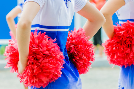 young female cheerleaders holding pom-poms during competitions