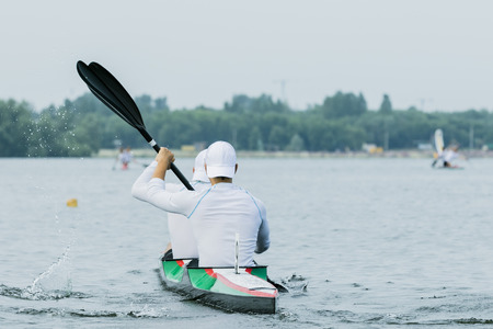 paddles: Two boys in sport kayak paddles on the water