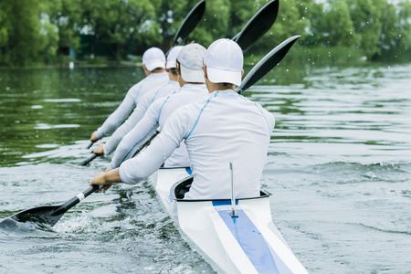 four boys in sport kayak paddles on the water 写真素材