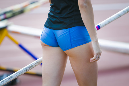 A female athlete competing in the pole vault at a track and field event