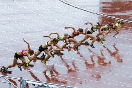 Chelyabinsk, Russia - July 10, 2015: young woman runners starting the race during Championship of Chelyabinsk on track and field athletics, Chelyabinsk, Russia - July 10, 2015