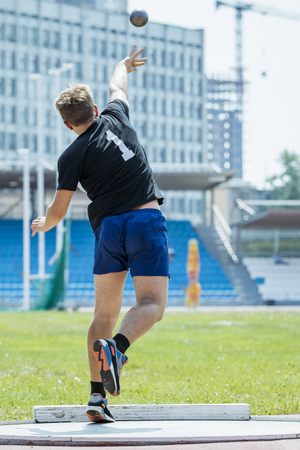 Rear view of athlete in sportswear  shot put