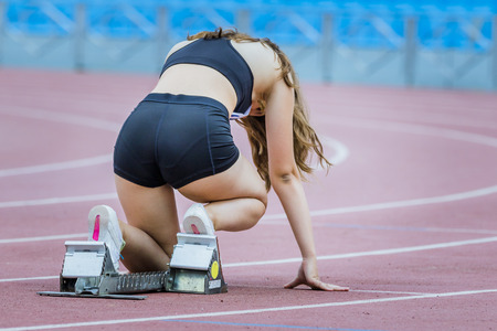 Girl athlete in starting position on an athletic track
