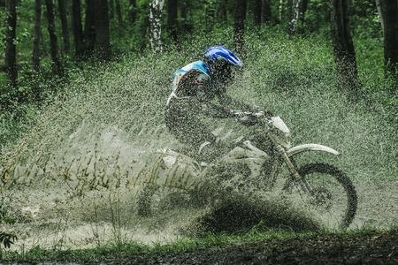 Motocross bike crossing creek, water splashing  in competition 스톡 콘텐츠