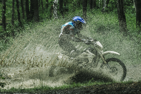 dirt road: Motocross bike crossing creek, water splashing  in competition Stock Photo