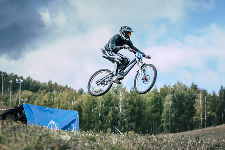 Magnitogorsk, Russia -  September 12, 2015: Athlete on a mountain bike is flying in a jump from a springboard during Urals Cup of downhill bike, Magnitogorsk, Russia -  September 12 Editorial
