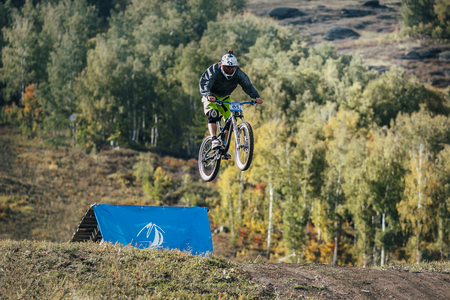 magnitogorsk: Magnitogorsk, Russia -  September 12, 2015: jump ski racer on the mountain bike in downhill race Urals Cup of downhill bike, Magnitogorsk, Russia -  September 12