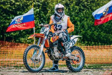 racer flag: Kyshtym, Russia - July 26, 2015: racer motocross preparing to start during the race Urals Cup of Enduro Forest watch, Kyshtym, Russia - July 26, 2015