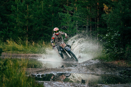 Kyshtym, Russia - July 26, 2015: A Motocross racer rides through a puddle during the race Urals Cup of Enduro
