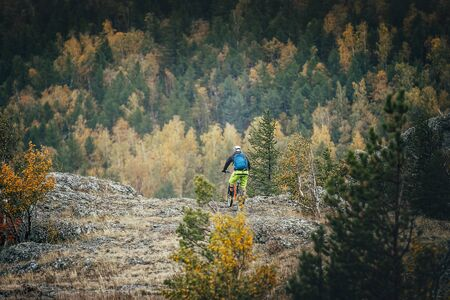 magnitogorsk: man mountain Biking on the mountain on the background of autumn forest