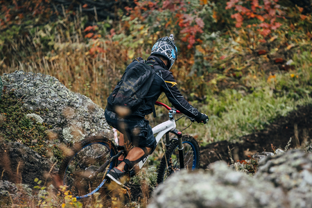 magnitogorsk: athlete on the bike to descend from the mountain along a narrow path between the rocks