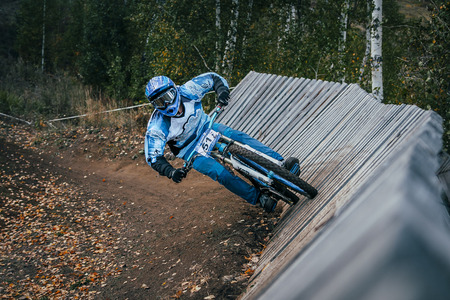 magnitogorsk: Magnitogorsk, Russia -  September 12, 2015: Cyclist riding a mountain bike downhill style during Urals Cup of downhill bike, Magnitogorsk, Russia -  September 12