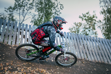 berm: Magnitogorsk, Russia -  September 12, 2015: Cyclist riding a mountain bike downhill style during Urals Cup of downhill bike, Magnitogorsk, Russia -  September 12