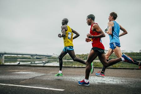 Omsk, Russia -  September 20, 2015: three leaders of the marathon running along the embankment of the Irtysh river during Siberian international marathon Editorial