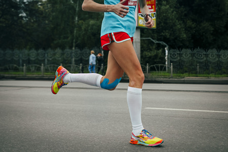 Girl running marathon, knees in blue kinesiology taping