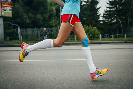 girl athlete running a marathon, knees in blue kinesiology taping