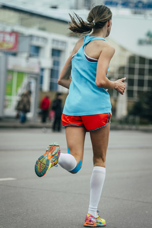 taping: young girl running a marathon, knees in blue kinesiology taping