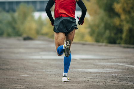 young man runs through streets. while running it on compression stockings and arm warmer