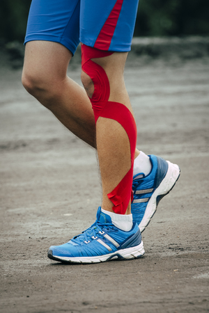 young man runs marathon, knee and Shin in red kinesiology taping Stock Photo