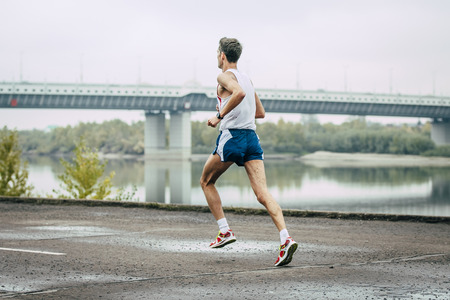 young man running along embankment of river during marathon Banque d'images