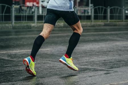 uomo sotto la pioggia: giovane atleta corre una maratona su una strada bagnata, gocce di pioggia