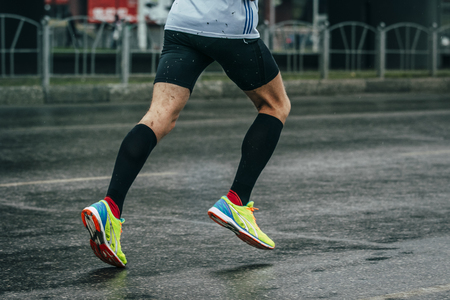 white socks: young man athlete runs a marathon on a wet road, rain drips