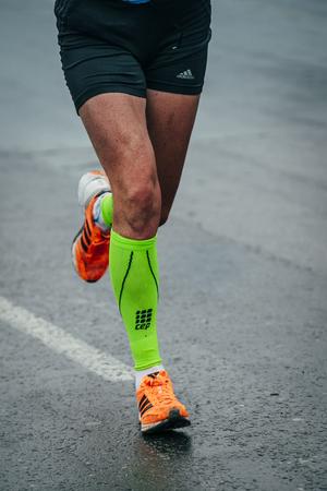 Omsk, Russia -  September 20, 2015: athlete runs on the wet asphalt during Siberian international marathon Editorial