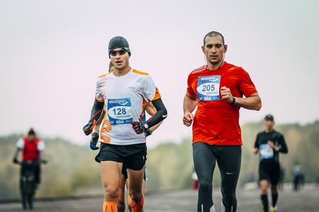 rivals rival rivalry season: Omsk, Russia -  September 20, 2015: two young men joggers run along embankment during Siberian international marathon