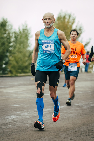 Omsk, Russia -  September 20, 2015: elderly athlete ahead of younger runner during Siberian international marathon Editorial